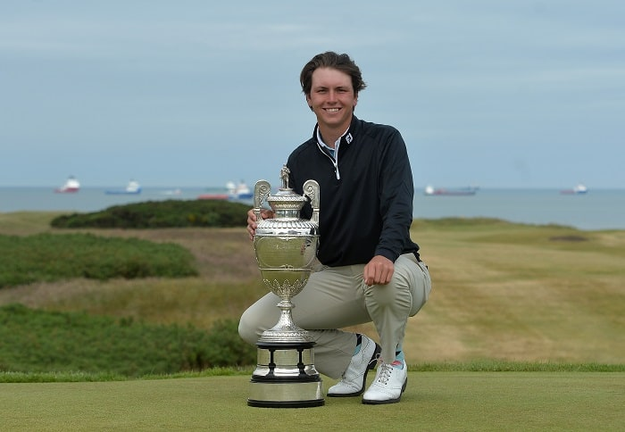 ABERDEEN, SCOTLAND - JUNE 23: Jovan Rebula of Republic of South Africa with the Amateur Championship trophy at the 18th green after beating Robin Dawson of Tramore in the Final of The Amateur Championship at Royal Aberdeen on June 23, 2018 in Aberdeen, Scotland. (Photo by Mark Runnacles/R&A/R&A via Getty Images)