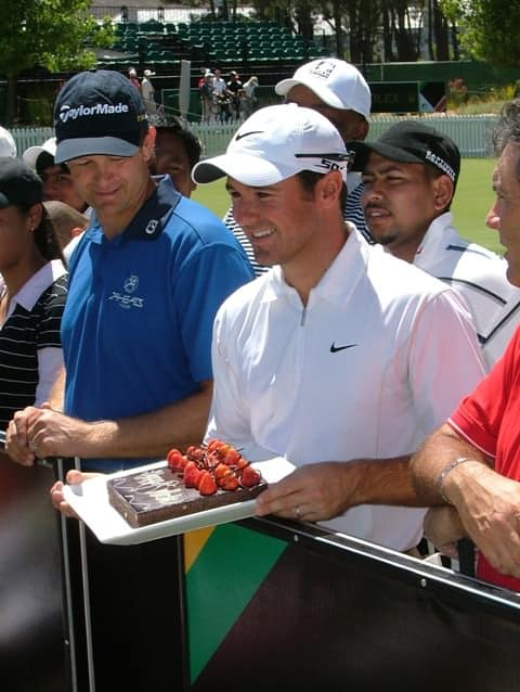Trevor Immelman receives his birthday cake as Retief Goosen looks on.